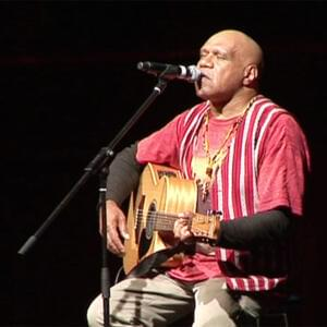 Photo of Archie Roach singing and playing an acoustic guitar