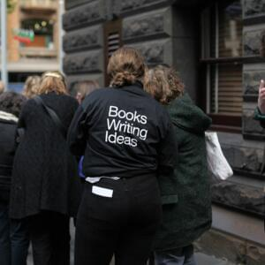 Photograph of a person wearing a t-shirt that says 'Books Writing Ideas' on its back, speaking with a person queued outside a bluestone building