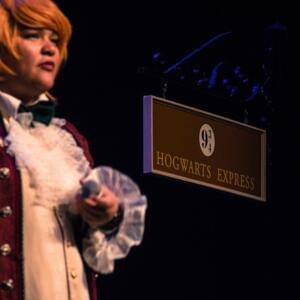 Photo of Candy Bowers in costume beside a sign that says 'Hogwarts Express'