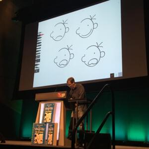 Photograph of Jeff Kinney at a lectern, drawing images of a cartoon face that are projected onto a screen behind him