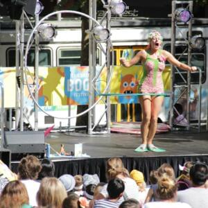 Photo of a performer in swimming trunks and flippers, on stage at State Library Victoria's lawns during Children's Book Festival 2014
