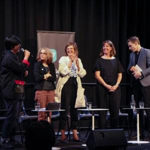 Photo of panellists standing and laughing