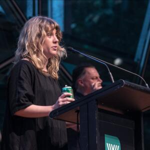 Photograph of Jennifer Down speaking at a lectern with a can of Victoria Bitter, with an Auslan interpreter beside her