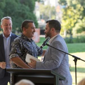Photograph of Michael Williams shaking Christos Tsiolkas's hand at a podium, with Martin Foley in the background