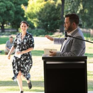 Michael Williams standing at a podium, with Helena Fox running toward him in the background across the grass