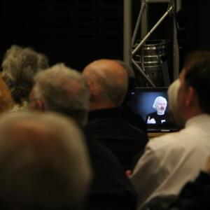 Photograph of a screen with Julian Assange's face on it, amid a crowd of people seated in an audience