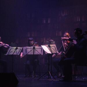 Photo of a string quartet performing in dim purple light