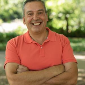 Photo of an olive-skinned short-haired man with arms folded over a salmon-coloured polo shirt, smiling widely at the camera