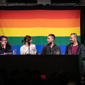 Photograph of four people on stage, sitting in front of a large rainbow flag
