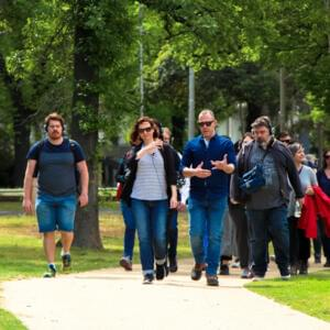 Photo of a crowd of people walking through the park wearing wireless headphones