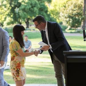 Photograph of Premier Daniel Andrews shaking Chloe Higgins's hand at a podium, with Michael Williams in the background