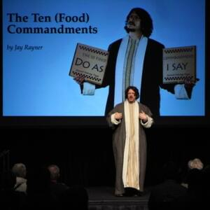 Photograph of a moustached Caucasian man wearing a robe in front of a projection screen that reads 'The Ten (Food) Commandments by Jay Rayner'