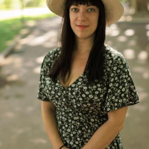 Photo of a light-skinned woman with medium-length dark hair, wearing a hat and a patterned dress, smiling slightly at the camera