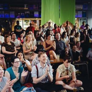 Photo of a casually-dressed audience of young writers clapping and smiling