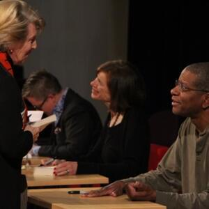 Photo of Ivan Coyote and Susan Faludi signing books while Paul Beatty speaks with an audience member