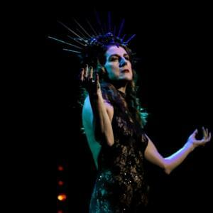 Photograph of a woman performing in low-lit darkness, wearing a lace bodysuit and a crown of long spines