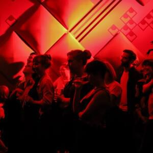 Photo of audience members bathed in red light at a bar