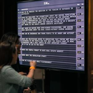 Photograph of a ticker screen of questions submitted by members of the audience