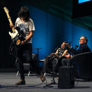 Photo of a person holding a guitar with hair covering their face, while two people sit on armchairs clapping and smiling