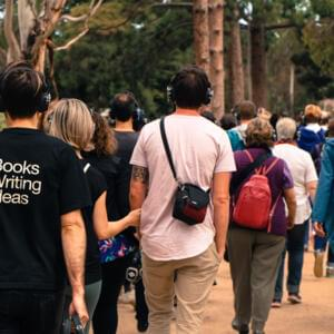 Photo of a group of headphone-wearing people walking in Royal Park
