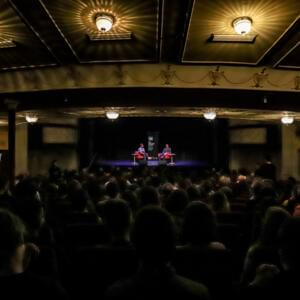 Photo of a crowd listening to a discussion at the Athenaeum Theatre