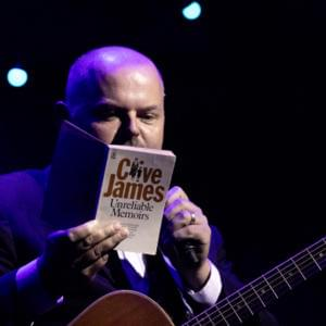 Photo of Casey Bennetto, reading from a Clive James book