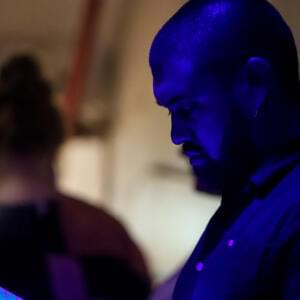 Photo of a bald and goateed man bathed in blue light, reading