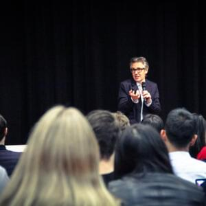 Photo of Ira Glass speaking with students